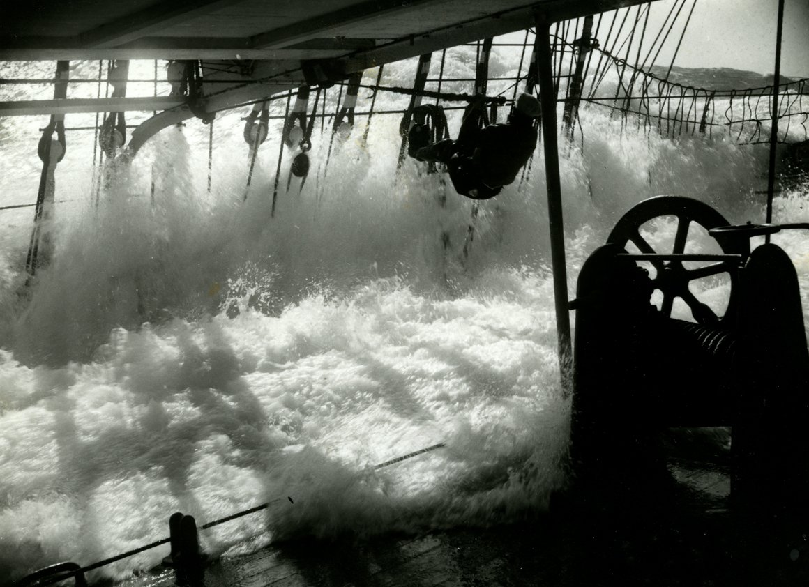 'A few seconds later. Jumping for the life-line as a big sea comes aboard'. Photograph by Eric Newby, 1938