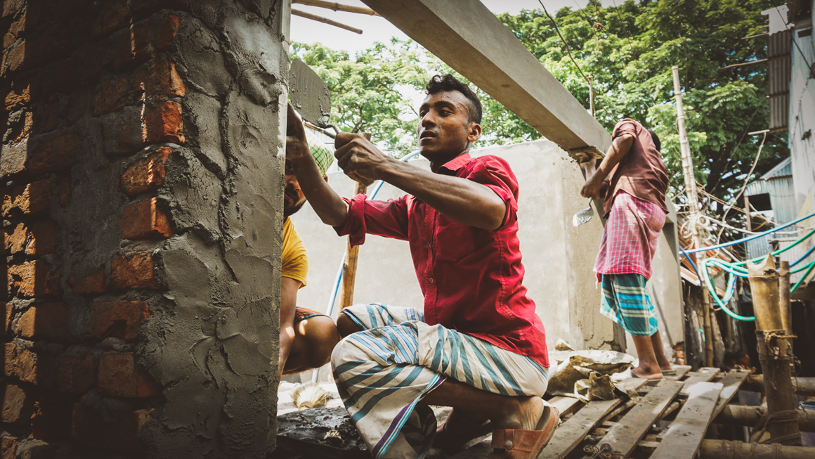 A man constructs a new building out of brick and cement in Ershadnagar. Image by Tasfiq Mahmood