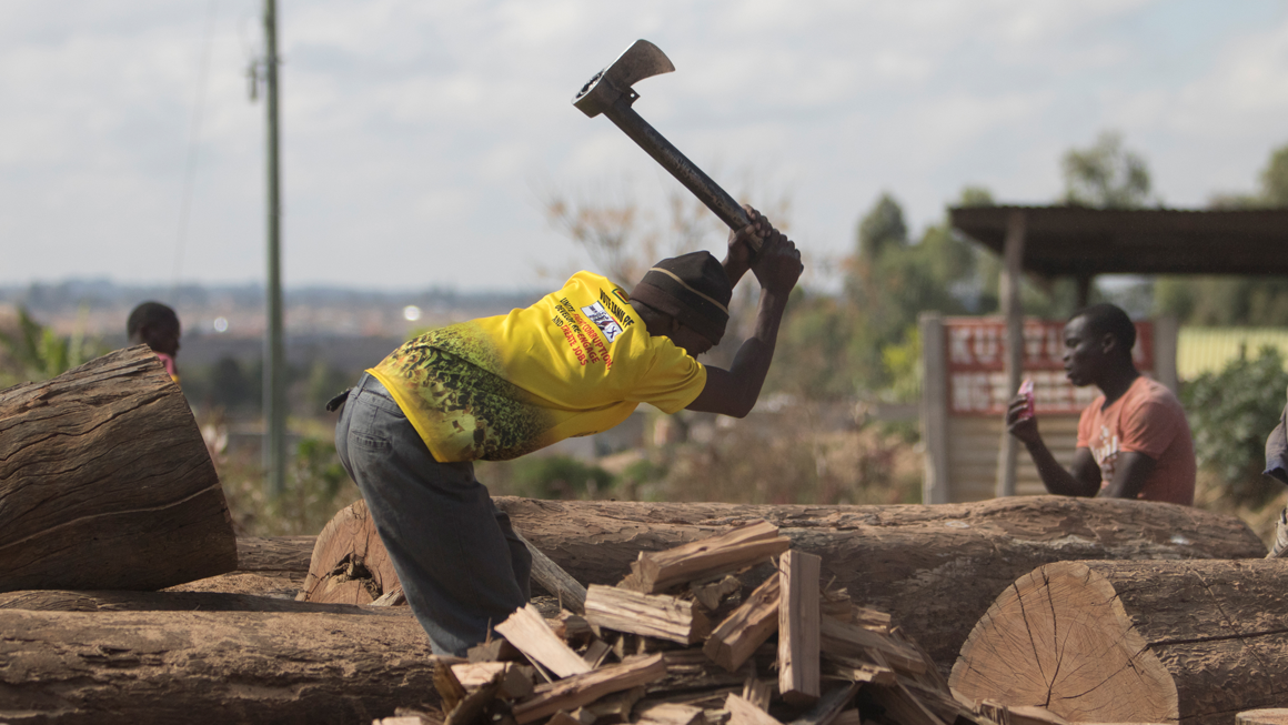 A man cutting wood for fuel in Epworth, Harare. Image by Wilfred Kajese