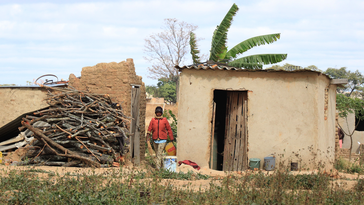 A woman walks between two shelters in Hopley, Harare. Image by Wilfred Kajese