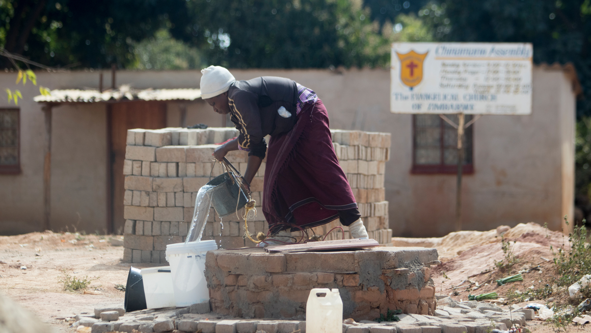 A woman collects water from a community well in Epworth. Image by Wifred Kajese