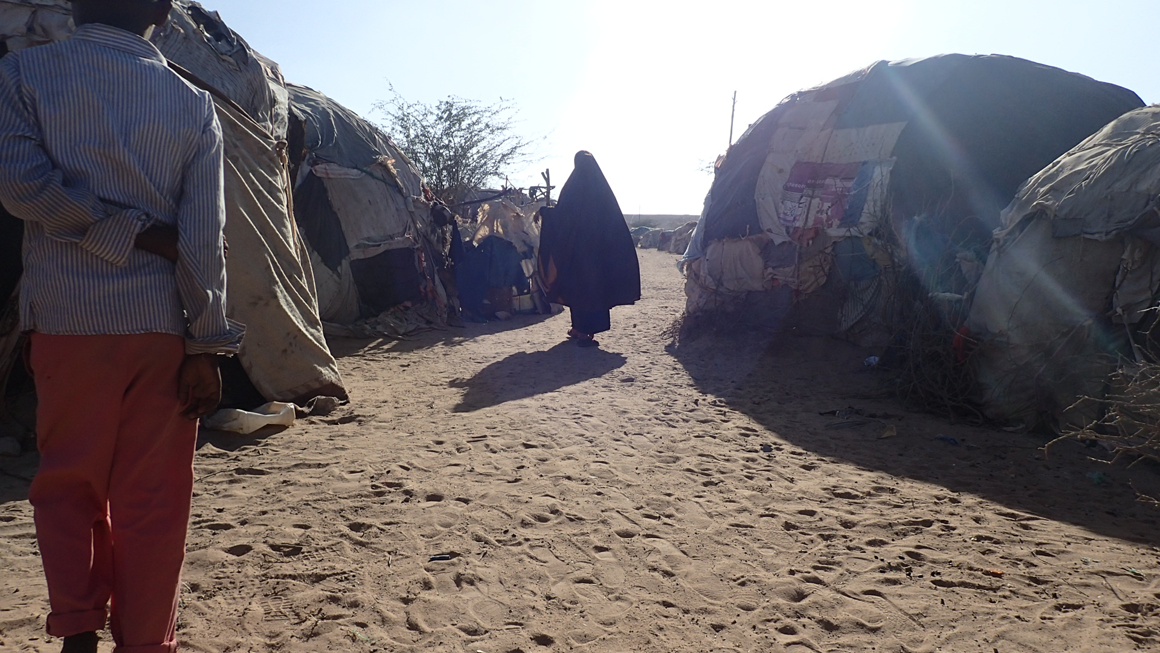 A woman walks in between the structures of Digaale camp. Image by Laura Hammond